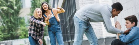Photo for Panoramic shot of african american boy in hoodie and jeans bulling boy and teenager shooting it and pointing with fingers - Royalty Free Image