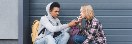 Photo for Panoramic shot of african american boy lighting cigarette of blonde teen - Royalty Free Image