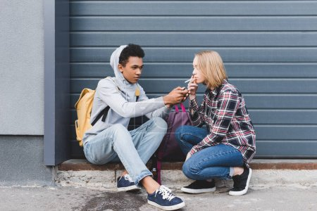 Photo for African american boy lighting cigarette of blonde and pretty teen - Royalty Free Image