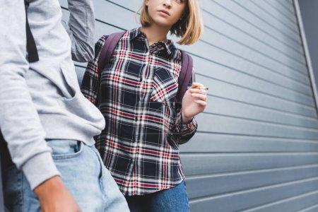 Photo pour Vue recadrée du garçon américain africain et de la cigarette blonde de tabagisme de l'adolescence - image libre de droit