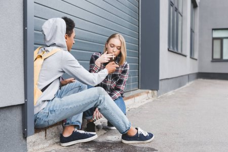 Photo pour Afro american garçon d'éclairage cigarette de blonde et jolie adolescente - image libre de droit