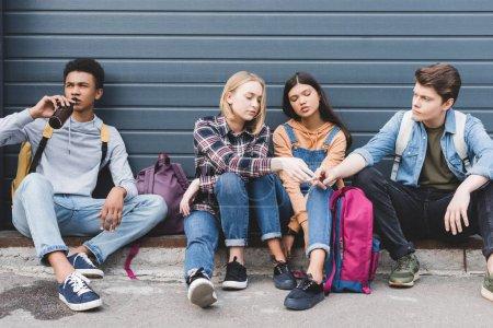 Photo pour Adolescents s'asseyant, buvant la bière de la bouteille en verre et retenant la cigarette - image libre de droit