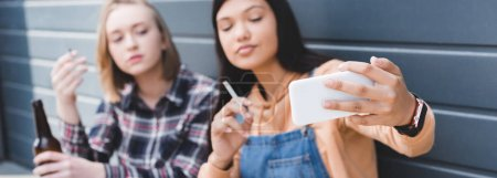 Photo for Panoramic shot of pretty friends smoking cigarettes and taking selfie - Royalty Free Image