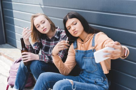 Photo for Selective focus of friends smoking cigarettes, holding beer and taking selfie - Royalty Free Image