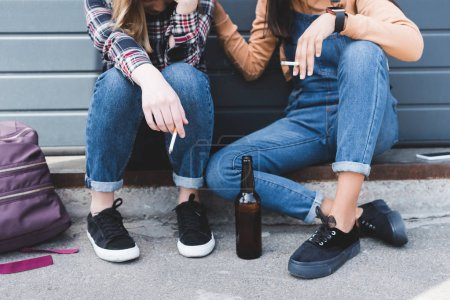 Foto de Vista recortada de los adolescentes fumando cigarrillos, sosteniendo la cerveza y sentado - Imagen libre de derechos