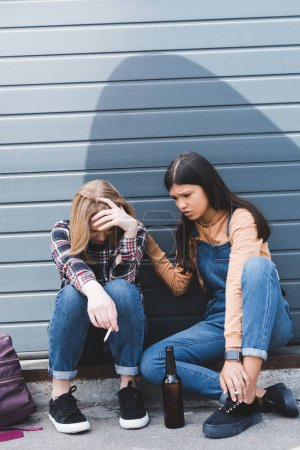 Photo for Sad and pretty teens sitting, talking and holding cigarettes - Royalty Free Image