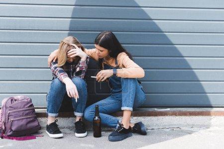 Foto de Molesto y bonito adolescentes sentados, hablando y sosteniendo cigarrillos - Imagen libre de derechos
