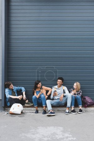 Photo for Teenagers sitting, drinking coffee from disposable cups and smiling - Royalty Free Image