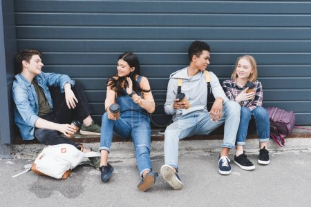 Photo for Teenagers sitting, drinking coffee from disposable cups and talking - Royalty Free Image