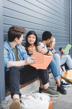Foto de Adolescentes sentados, hablando, sosteniendo vasos de papel y libros fuera - Imagen libre de derechos