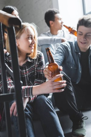 Photo pour Smiling teenagers sitting on stairs, holding beer and talking - image libre de droit