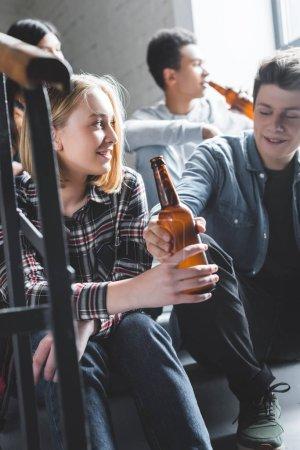 Foto de Adolescentes sonrientes sentados en las escaleras, sosteniendo cerveza y hablando - Imagen libre de derechos