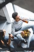 """Постер, картина, фотообои """"high angle view of teenagers talking, sitting on stairs and drinking beer """""""