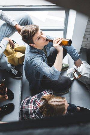 Foto de Vista de ángulo alto de los adolescentes sentados en las escaleras y bebiendo cerveza - Imagen libre de derechos