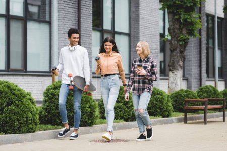 smiling teenagers walking and holding disposable cups and skateboard