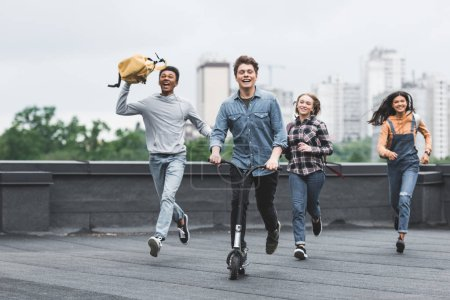 Photo for Playful and smiling teenagers running on roof and riding scooter - Royalty Free Image