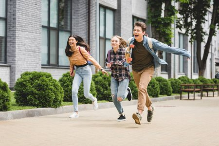 Foto de Playful and happy teenagers running with skateboard and smiling - Imagen libre de derechos