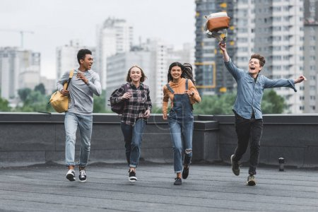 Foto de Playful and happy teenagers running and smiling on roof - Imagen libre de derechos