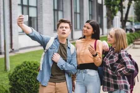 Photo pour Adolescents heureux retenant le smartphone, prenant le selfie et souriant - image libre de droit