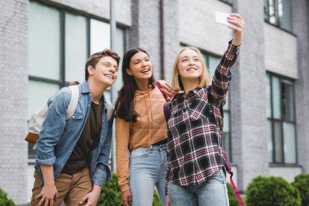 Photo pour Adolescents heureux retenant le smartphone, prenant le selfie et souriant à l'extérieur - image libre de droit