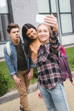 Photo pour Adolescents positifs retenant le smartphone, prenant le selfie et souriant à l'extérieur - image libre de droit