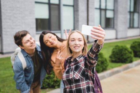 Foto de Adolescentes felices sosteniendo teléfono inteligente, tomando selfie y sonriendo fuera - Imagen libre de derechos