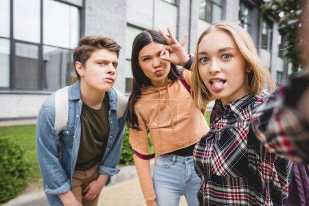 Photo pour Adolescents positifs prenant selfie et montrant geste ok à l'extérieur - image libre de droit
