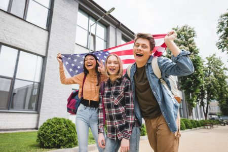 Photo for Happy teenagers smiling, holding american flag and looking at camera - Royalty Free Image
