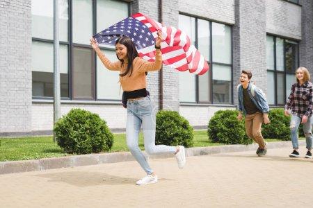 Foto de Adolescentes felices sonriendo, sosteniendo la bandera americana y corriendo fuera - Imagen libre de derechos