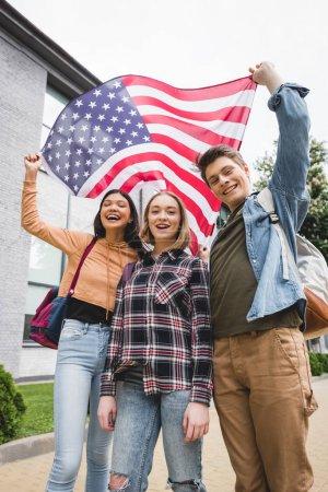 Foto de Adolescentes felices sonriendo, sosteniendo la bandera americana y mirando la cámara - Imagen libre de derechos