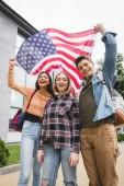 """Постер, картина, фотообои """"счастливые подростки улыбаются, держа американский флаг и глядя в камеру"""""""