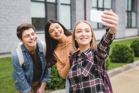 Photo for Cheerful teenagers holding smartphone, taking selfie and smiling outside - Royalty Free Image
