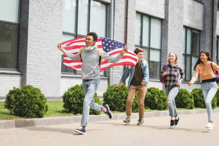 Photo for Happy teenagers smiling, holding american flag and running outside - Royalty Free Image