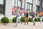 """Постер, картина, фотообои """"счастливые подростки улыбаются, держа американский флаг и работает на улице"""""""