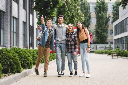 Foto de Adolescentes felices sosteniendo la bandera americana y señalando con el dedo - Imagen libre de derechos