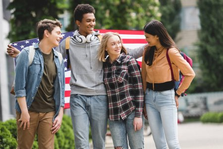 Photo for Happy and smiling teenagers holding american flag and talking - Royalty Free Image