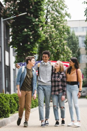 Photo for Smiling and happy teenagers holding american flag and talking - Royalty Free Image