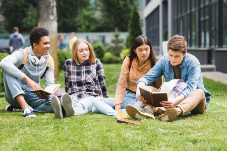 Photo pour Adolescents de sourire s'asseyant sur l'herbe et lisant le livre à l'extérieur - image libre de droit