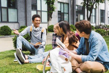 Photo pour Adolescents souriants s'asseyant sur l'herbe, parlant et retenant des livres - image libre de droit