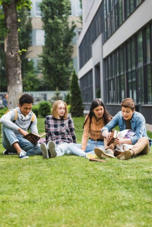 Photo for Smiling teenagers sitting on grass and reading books outside - Royalty Free Image