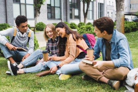 Photo pour Adolescents souriants s'asseyant sur l'herbe, parlant, retenant des livres et des tasses en papier - image libre de droit