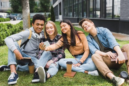 Photo pour Adolescents souriants et heureux s'asseyant sur l'herbe et prenant le selfie - image libre de droit