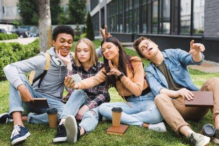 Photo pour Souriant et heureux adolescents assis sur l'herbe et prendre selfie - image libre de droit
