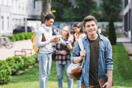 Foto de Adolescente sonriente sosteniendo libro y mochila y mirando a la cámara - Imagen libre de derechos