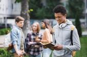 "Постер, картина, фотообои ""smiling african american teenager in hoodie with headphones reading book"""
