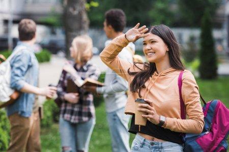 Photo pour Adolescent de sourire et brunette retenant la cuvette de papier avec le café et regardant loin - image libre de droit