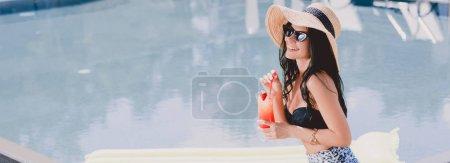Photo pour Belle jeune femme brune dans le maillot de bain, chapeau de paille et lunettes de soleil souriant tout en retenant le cocktail près de la piscine avec le flotteur de piscine, projectile panoramique - image libre de droit