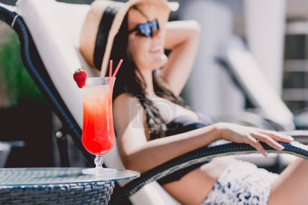 Photo for Selective focus of cool cocktail with strawberry on table with beautiful smiling brunette young woman sunbathing on background - Royalty Free Image
