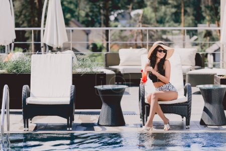 Photo for Beautiful brunette young woman in swimsuit, straw hat and sunglasses holding cocktail while sitting on sunbed near swimming pool - Royalty Free Image