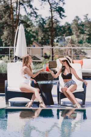 Photo for Happy brunette and blonde women in swimsuits drinking cocktails near swimming pool - Royalty Free Image